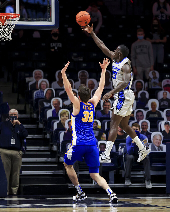Xavier forward Zach Freemantle (32) defends as Creighton forward Damien Jefferson drives to the basket in the first half of an NCAA college basketball game, Saturday, Feb. 27, 2021, in Cincinnati. (AP Photo/Aaron Doster)