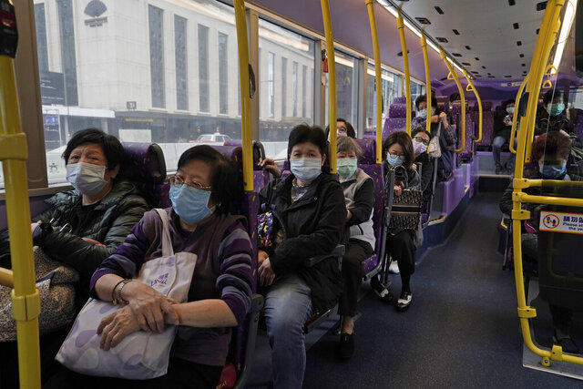Passengers wears face masks as a precaution against the COVID-19 while sitting in a bus in Hong Kong, Thursday, Feb. 27, 2020. (AP Photo/Kin Cheung)