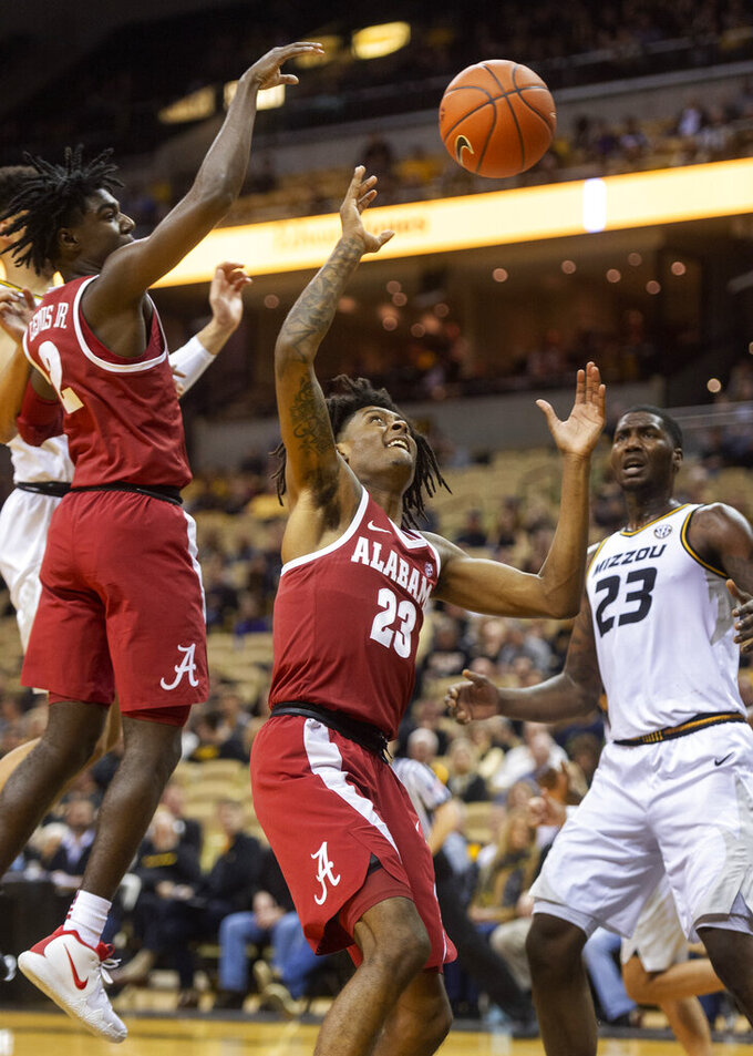 Alabama's John Petty, center, pulls down a rebound between teammate Kira Lewis Jr., left, and Missouri's Jeremiah Tilmon, right, during the first half of an NCAA college basketball game, Wednesday, Jan. 16, 2019, in Columbia, Mo. (AP Photo/L.G. Patterson)