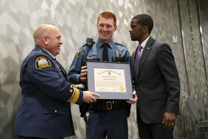 In this April 22, 2019 photo, St. Paul Police Officer Alexander Graham is presented with an honorable mention award for Officer of the Year from St. Paul Police Chief Todd Axtell, left, and St. Paul Mayor Melvin Carter in St. Paul, Minn. Mayor Carter demanded an internal police investigation into the arrest of a 13-year-old black girl, after video showing her shrieking and struggling as two white, male officers try to handcuff her sparked an angry backlash on social media. One of the officers, Alexander Graham, is the subject of an internal affairs investigation, but it's not clear if it's related to the girl's arrest, the St. Paul Pioneer Press reported. (Renee Jones Schneider/Star Tribune via AP)
