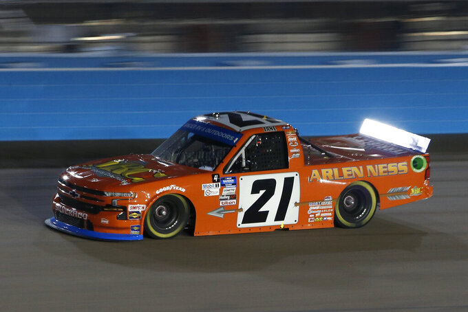 Zane Smith (21) races through Turn 4 during the NASCAR Truck Series auto race at Phoenix Raceway, Friday, Nov. 6, 2020, in Avondale, Ariz. (AP Photo/Ralph Freso)