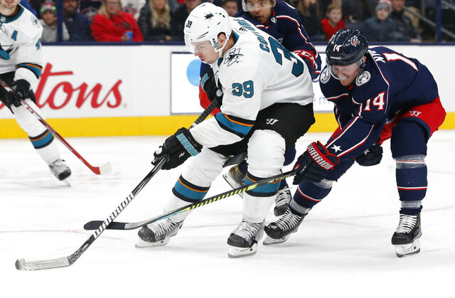 FILE - In this Jan. 4, 2020, file photo, San Jose Sharks' Logan Couture, left, skates the puck upice as Columbus Blue Jackets' Gustav Nyquist, of Sweden, defends during the third period of an NHL hockey game in Columbus, Ohio. The Sharks never managed to climb out of the deep hole they dug with a slow start last season. Avoiding the same fate this year is a high priority for the team, especially the condensed 56-game schedule and the extended road trip they are on to start this season. (AP Photo/Jay LaPrete, File)
