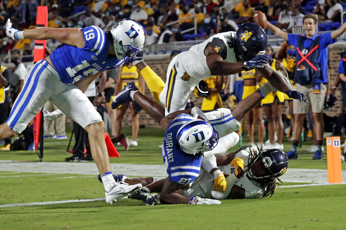 Duke running back Mataeo Durant (21) goes in for a touchdown against North Carolina A&T defensive back Miles Simon (4), bottom, and linebacker Joseph Stuckey (8) during the first half of an NCAA college football game in Durham, N.C., Friday, Sept. 10, 2021. (AP Photo/Chris Seward)
