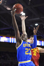 UCLA guard Prince Ali, left, shoots as Southern California forward Nick Rakocevic defends during the second half of an NCAA college basketball game Saturday, Jan. 11, 2020, in Los Angeles. USC won 74-63. (AP Photo/Mark J. Terrill)