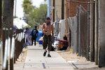 A pedestrian walks along next to a homeless encampment as temperatures continue to soar past 115-degrees Thursday, June 17, 2021, in Phoenix. (AP Photo/Ross D. Franklin)
