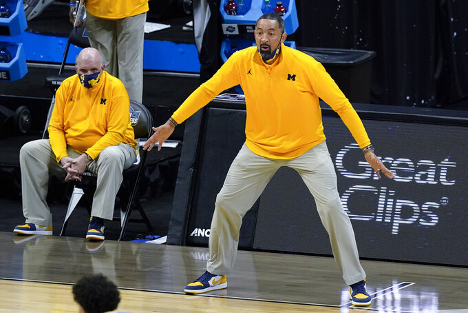 Michigan head coach Juwan Howard reacts to a play as assistant coach Phil Martelli looks on from the bench during the first half of an Elite 8 game against UCLA in the NCAA men's college basketball tournament at Lucas Oil Stadium, Tuesday, March 30, 2021, in Indianapolis. (AP Photo/Darron Cummings)