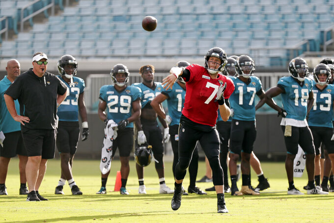 Jacksonville Jaguars quarterback Nick Foles (7) throws a pass as head coach Doug Marrone, far left, looks on during an NFL football practice at the teams stadium, Friday, Aug. 2, 2019, in Jacksonville, Fla. (AP Photo/John Raoux)