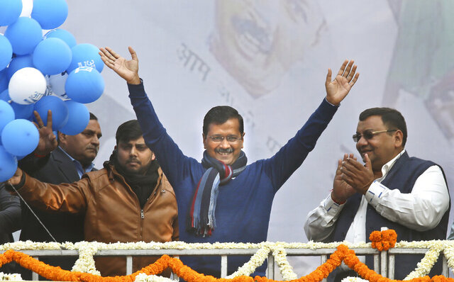 Incumbent Delhi Chief Minister Arvind Kejriwal, center, waves at Aam Aadmi Party, or