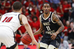 Wake Forest guard Torry Johnson (11) brings the ball up as he is pressured by Louisville guard Samuell Williamson (10) during the first half of an NCAA college basketball game Wednesday, Feb. 5, 2020, in Louisville, Ky. (AP Photo/Wade Payne)