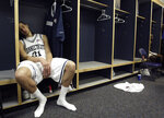 FILE - In this March 26, 2006, file photo, Connecticut's Josh Boone sits in the locker room after his team's 86-84 overtime loss to George Mason in the NCAA basketball tournament regional championship game in Washington. (Preston Keres/The Washington Post via AP, File)