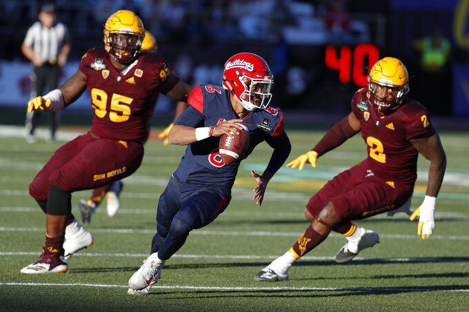 Fresno State quarterback Marcus McMaryion runs from Arizona State defensive players during the second half of the Las Vegas Bowl NCAA college football game, Saturday, Dec. 15, 2018, in Las Vegas. (AP Photo/John Locher)