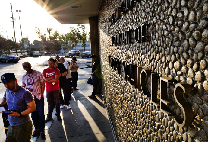 FILE - In this Tuesday, Aug. 7, 2018, file photo, people line up at the California Department of Motor Vehicles prior to opening in the Van Nuys section of Los Angeles. A Republican lawyer who has waged lawsuits on behalf of the Trump administration is suing California and the state DMV, saying the agency is failing to verify whether non-citizens are being registered to vote. (AP Photo/Richard Vogel, File)