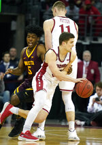 Wisconsin's Tyler Wahl, front, maneuvers around Minnesota's Marcus Carr (5) with teammate Micah Potter (11) blocking during the first half of an NCAA college basketball game Sunday, March 1, 2020, in Madison, Wis. (AP Photo/Andy Manis)