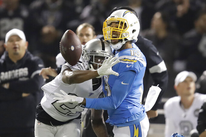 Oakland Raiders cornerback Trayvon Mullen, left, breaks up a pass intended for Los Angeles Chargers wide receiver Keenan Allen during the first half of an NFL football game in Oakland, Calif., Thursday, Nov. 7, 2019. (AP Photo/Ben Margot)
