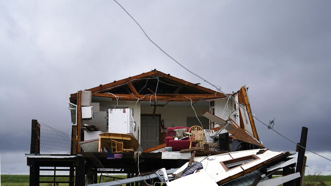 Storm clouds from Tropical Storm Nicholas are seen behind a home that was destroyed by Hurricane Ida, in Pointe-aux-Chenes, La., Tuesday, Sept. 14, 2021. (AP Photo/Gerald Herbert) 985-850-1149