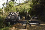 A soldier walks along the road where two vehicles where incinerated during a skirmish between illegal armed groups in which at least five people were killed in Jamundi, southwest Colombia, Friday, Jan. 17, 2020. Authorities say rebels with the former Revolutionary Armed Forces of Colombia operate in the area and may have been involved. (AP Photo/Christian EscobarMora)