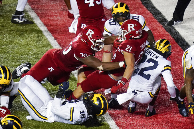 Rutgers' Johnny Langan (21) rushes against Michigan's Luiji Vilain (18) and Gemon Green (22) for a touchdown during the first half of an NCAA college football game Saturday, Nov. 21, 2020, in Piscataway, N.J. (AP Photo/Frank Franklin II)
