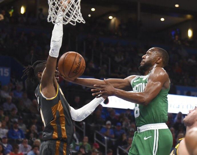 Boston Celtics guard Kemba Walker (8) shoots around Oklahoma City Thunder forward Nerlens Noel (9) in the second half of an NBA basketball game, Sunday, Feb. 9, 2020, in Oklahoma City. (AP Photo/Kyle Phillips)