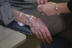 In this Nov, 22, 2019, photo, Charles Flagg, who is stricken with Alzheimer's disease, rests his arm during his infusion while participating in a study on the drug Aducanumab at Butler Hospital in Providence, R.I. New results were released on the experimental medicine whose maker claims it can slow the decline of Alzheimer's disease, the most common form of dementia. (AP Photo/Charles Krupa)