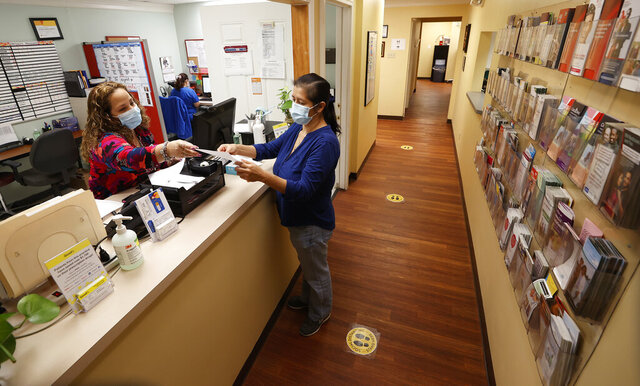 Eleanor Sanchez, manager of CrossOver Healthcare Ministry's Richmond clinic, helps Sara Eunice Cruz check out Tuesday, Oct. 27, 2020. (Alexa Welch Edlund/Richmond Times-Dispatch via AP)