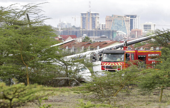 Rescue teams attend the scene where a plane crashed while taking off from Wilson airport in Nairobi, Kenya Friday, Oct. 11, 2019. The operator Silverstone Air said all passengers and crew have safely disembarked with the cause of the crash not yet known. (AP Photo/Khalil Senosi)