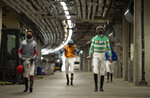 Jockeys wearing face masks to protect against coronavirus, walk through the service tunnel from the auxilary weighing room towards the paddock during day one of Royal Ascot at Ascot Racecourse, in Ascot, England, Tuesday June 16, 2020.  The meeting, which is one of the country's most high-profile horse racing meetings will take place behind closed doors.  (Edward Whitaker/PA via AP)