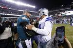 Philadelphia Eagles quarterback Carson Wentz, left, meets with Dallas Cowboys quarterback Dak Prescott after of an NFL football game Sunday, Dec. 22, 2019, in Philadelphia. (AP Photo/Michael Perez)