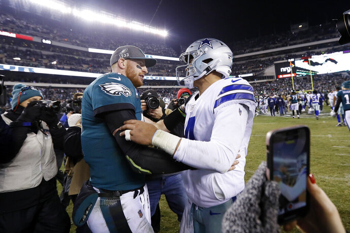 Philadelphia Eagles quarterback Carson Wentz, left, meets with Dallas Cowboys quarterback Dak Prescott after of an NFL football game Sunday, Dec. 22, 2019, in Philadelphia. (AP Photo/Michael Perez)
