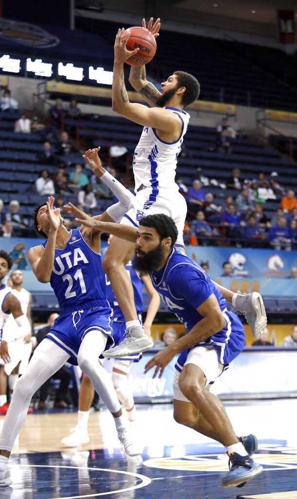 Georgia State guard D'Marcus Simonds (15) goes up to the basket between Texas-Arlington guards Pedro Castro (21) and Brian Warren during the second half of an NCAA college basketball game for the Sun Belt Conference men's tournament championship in New Orleans, Sunday, March 17, 2019. Georgia State won 73-64. (AP Photo/Tyler Kaufman)