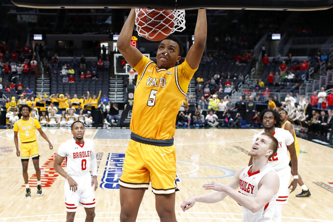 Valparaiso's Donovan Clay (5) dunks as Bradley's Danya Kingsby (0) and Nate Kennell, right, watch during the first half of an NCAA college basketball game in the championship of the Missouri Valley Conference men's tournament Sunday, March 8, 2020, in St. Louis. (AP Photo/Jeff Roberson)