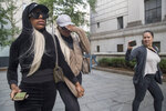 Shannade Clermont, center, and her twin sister Shannon are followed by a reporter as they leave Federal court in New York after her arraignment, Wednesday, July 11, 2018. Shannade Clermont, a former cast member of the television reality series
