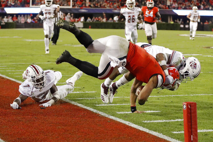 Georgia quarterback Justin Fields (1) is stopped short of the end zone by Massachusetts safety Brice McAllister (2) during the second half of an NCAA college football game Saturday, Nov. 17, 2018, in Athens, Ga. (AP Photo/John Bazemore)