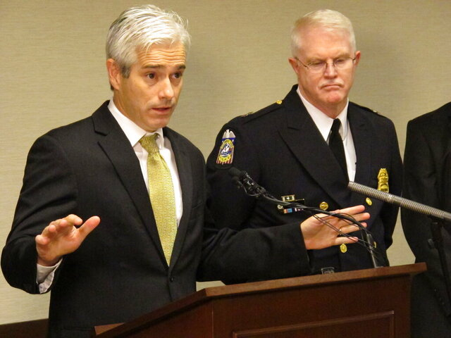 FILE - In this Oct. 28, 2014, file photo, assistant U.S. attorney Dave DeVillers, left, discusses updated charges against members of an alleged gang as Columbus Deputy Police Chief Ron Gray listens during a news conference in Columbus, Ohio. A federal indictment accuses Larry Dean Porter of exchanging drugs for sexual access to children of drug-addicted parents. The indictment says Porter repeatedly traded drugs for sex with three girls, with several other adults helping transport the victims to Porter's house. Porter both raped the girls and filmed himself raping them, U.S. Attorney Dave DeVillers said Wednesday, June 24, 2020. (AP Photo/Andrew Welsh-Huggins, File)