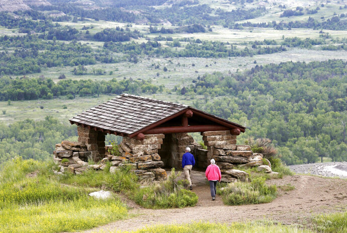 FILE - In this June 11, 2014, file photo, visitors hike to a stone lookout over the Little Missouri River inside the Theodore Roosevelt National Park, located in the Badlands of North Dakota. Anemic funding, alleged unpaid work and legal fights are hobbling developers of a proposed $800 million oil refinery near the park in western North Dakota. But the project manager for Meridian Energy Group's Davis Refinery, which has drawn criticism from environmental groups and others who worry it would add to pollution near the national park, insists it will be built. (AP Photo/Charles Rex Arbogast, File)