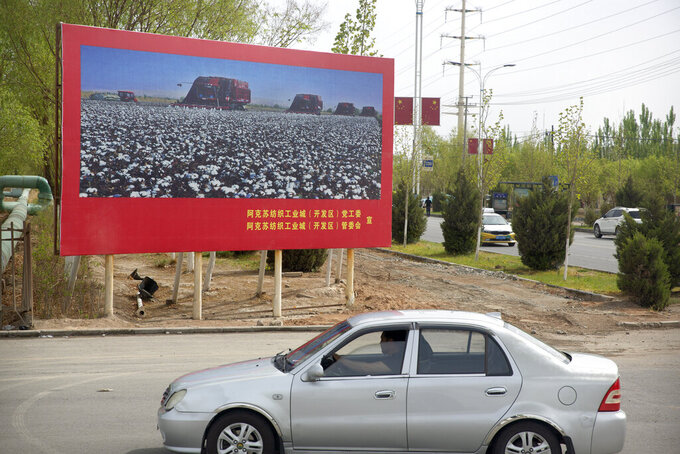 A car is driven past a billboard showing machines harvesting cotton outside a Huafu Fashion plant, as seen during a government organized trip for foreign journalists, in Aksu in western China's Xinjiang Uyghur Autonomous Region, Tuesday, April 20, 2021. A backlash against reports of forced labor and other abuses of the largely Muslim Uyghur ethnic group in Xinjiang is taking a toll on China's cotton industry, but it's unclear if the pressure will compel the government or companies to change their ways. (AP Photo/Mark Schiefelbein)