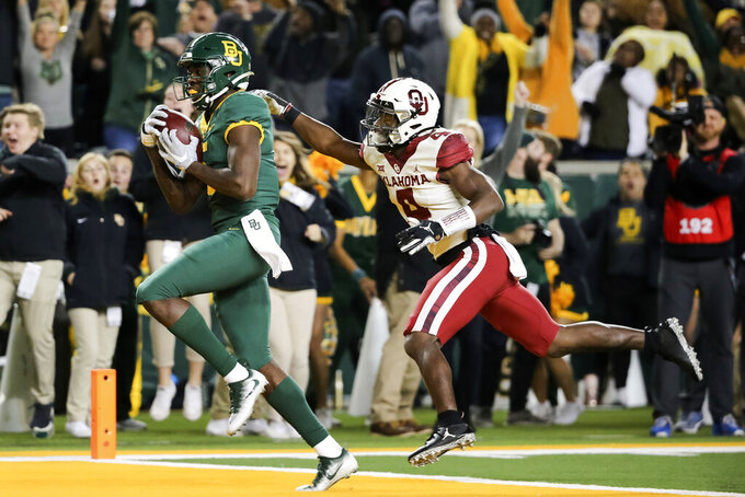 Baylor wide receiver Denzel Mims, left, makes a 30-yard touchdown catch as Oklahoma cornerback Jaden Davis, right, defends during the first half of an NCAA college football game in Waco, Texas, Saturday, Nov. 16, 2019. (AP Photo/Ray Carlin)