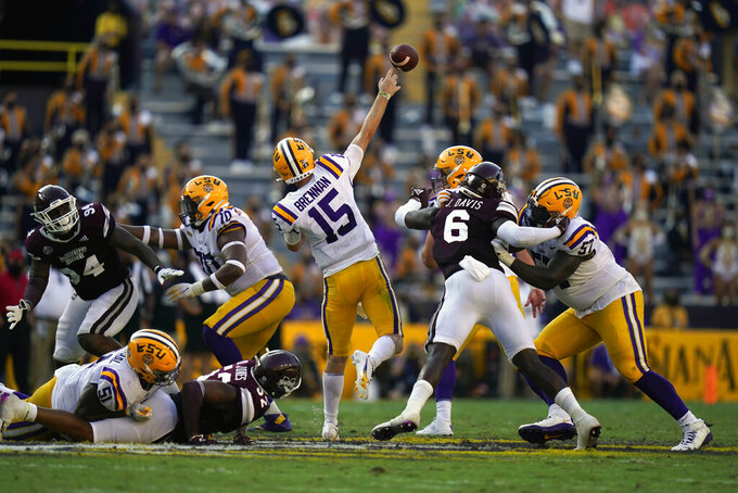 LSU quarterback Myles Brennan (15) passes under pressure from Mississippi State safety Jordan Davis (6), defensive end Kobe Jones (52) and defensive tackle Jaden Crumedy (94) in the second half an NCAA college football game in Baton Rouge, La., Saturday, Sept. 26, 2020. Mississippi State won 44-34. (AP Photo/Gerald Herbert)