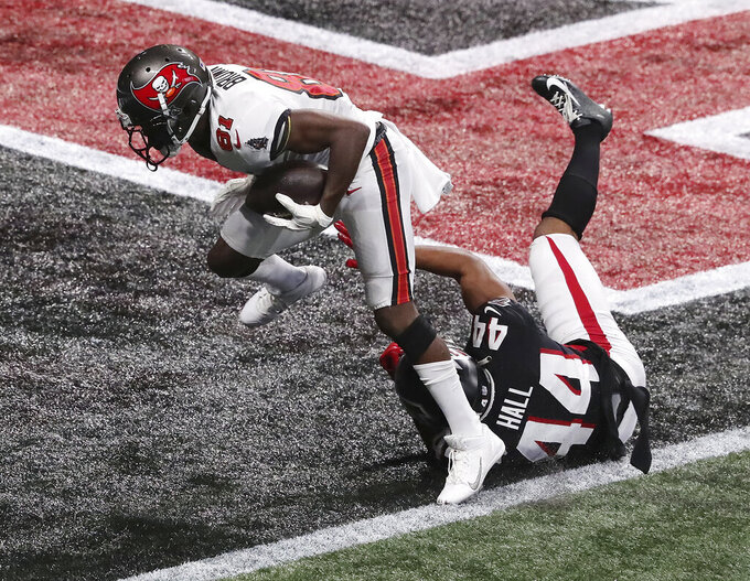 Tampa Bay Buccaneers wide receiver Antonio Brown, top,  gets past Atlanta Falcons cornerback Tyler Hall for what proved to be the winning touchdown in the final minutes of an NFL football game Sunday, Dec. 20, 2020, in Atlanta. (Curtis Compton/Atlanta Journal-Constitution via AP)