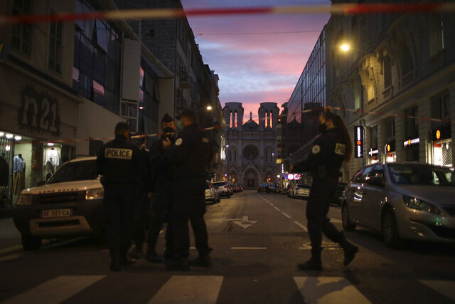 Police work behind a restricted zone near the Notre Dame church in Nice, southern France, after a knife attack took place on Thursday, Oct. 29, 2020. An attacker armed with a knife killed at least three people at a church in the Mediterranean city of Nice, prompting the prime minister to announce that France was raising its security alert status to the highest level. (AP Photo/Daniel Cole)
