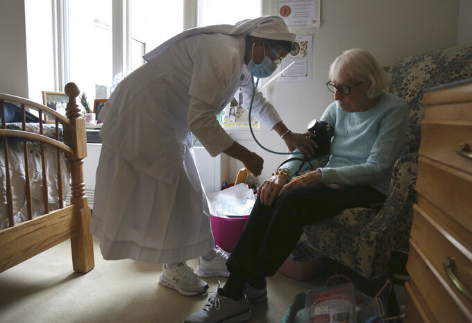 Sister Rose Nellivila checks the blood pressure of Lorraine Catney, a resident of Villa Angela at St. Anne Home nursing facility in Greensburg, Pa., Thursday, March 25, 2021. (AP Photo/Jessie Wardarski)