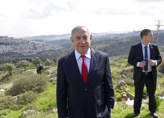 Israeli Prime Minister Benjamin Netanyahu stands at an overview of the West Bank Israeli settlement of Har Homa where he announced a new neighborhood is to be built, Thursday, Feb. 20, 2020. (Debbie Hill/Pool via AP)