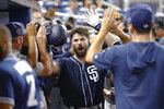 San Diego Padres' Austin Hedges, center, is congratulated by teammates after he hit a two-run home run during the fourth inning of the team's baseball game against the Miami Marlins, Wednesday, July 17, 2019, in Miami. (AP Photo/Wilfredo Lee)