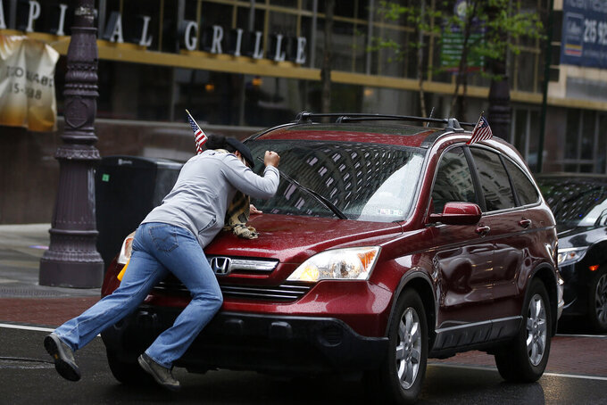 A counter-protester beats on the hood of a car as he is pushed back after blocking a drive-by rally to reopen the country and economy outside City Hall in Philadelphia, Friday, May 8, 2020. (AP Photo/Matt Slocum)