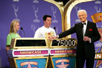 """FILE - Host Bob Barker appears with contestants during filming of a special prime-time episode of """"The Price Is Right,"""" in Los Angeles on April 17, 2007. The longest-running game show in television history is celebrating it's 50th season. (AP Photo/Kevork Djansezian, File)"""