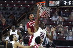 South Carolina center Tre-Vaughn Minott (50) dunks against Arkansas guard Desi Sills (3) during the first half of an NCAA college basketball game Tuesday, March 2, 2021, in Columbia, S.C. (AP Photo/Sean Rayford)
