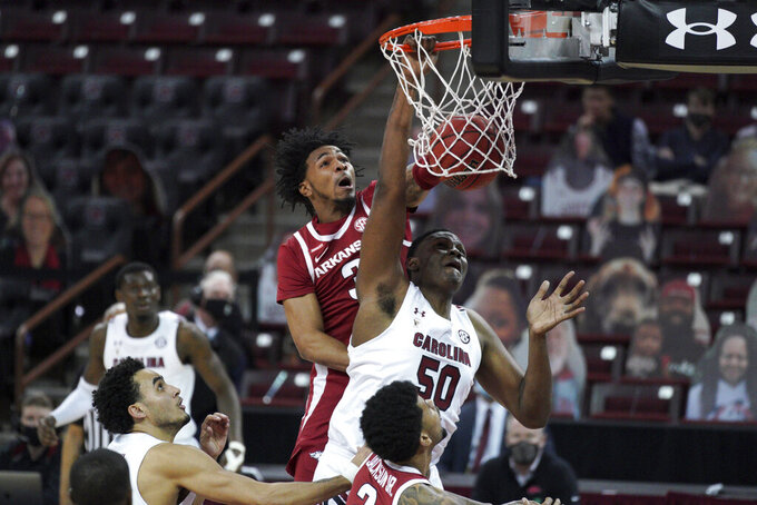 South Carolina center Tre-Vaughn Minott (50) dunks against Arkansas guard Desi Sills (3) during the first half of an NCAA college basketball game Tuesday, March 2, 2021, in Columbia, S.C. (AP Photo/Sean Rayford)