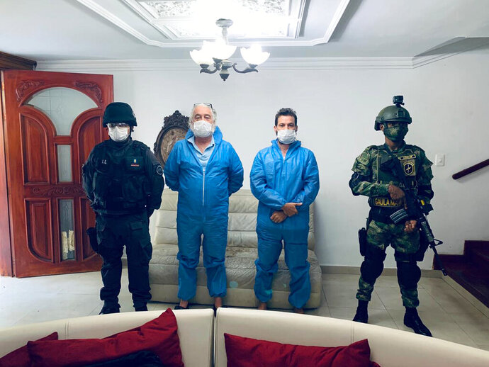 In this photo released by Colombia's Prosecutor's Press Office, a police officer and a soldier flank Mark Grennon, second left, and his son Joseph Grennon, during a raid in Santa Marta, Colombia, Tuesday, Aug. 11, 2020. Colombian officials say they arrested the two Florida men wanted in the United States on charges they illegally sold a bleachlike chemical as a miracle cure for the new coronavirus and other diseases. (Colombia's Prosecutor's Press Office via AP)