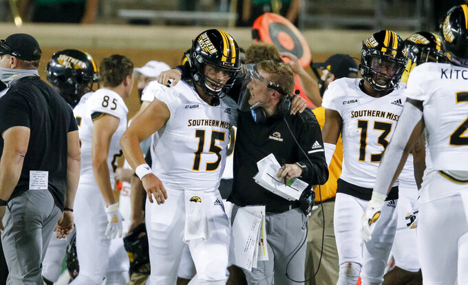 Southern Mississippi quarterback Jack Abraham (15) is congratulated by interim head coach Scotty Walden after a scoring drive during the second half of an NCAA college football game against North Texas on Saturday, Oct. 3, 2020, in Denton, Texas. (AP Photo/Brandon Wade)