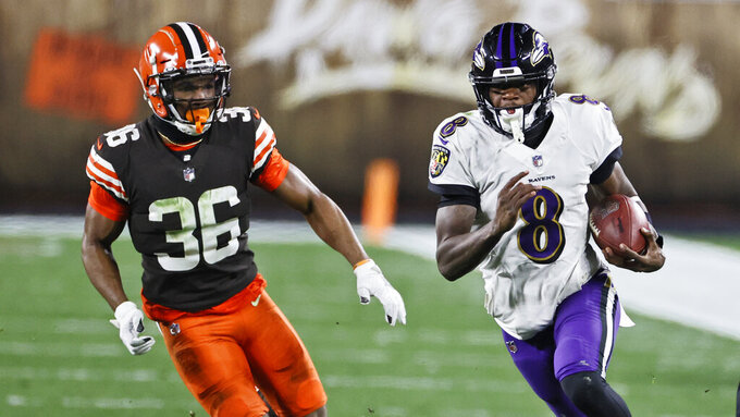Baltimore Ravens quarterback Lamar Jackson (8) scrambles under pressure from Cleveland Browns cornerback M.J. Stewart Jr. (36) during the second half of an NFL football game, Monday, Dec. 14, 2020, in Cleveland. (AP Photo/Ron Schwane)