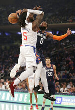 New York Knicks guard Kadeem Allen (0), right, fouls Los Angeles Clippers forward Montrezl Harrell (5) who drives to the basket during the first half of an NBA basketball game, Sunday, March 24, 2019, in New York. (AP Photo/Seth Wenig)